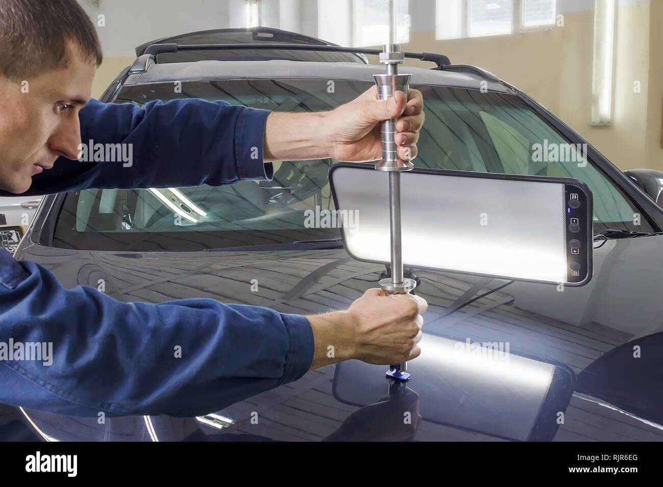 Professional mechanic removes dents on the car body Stock Photo