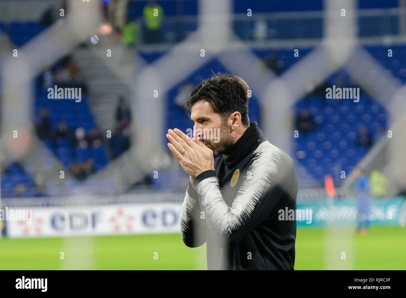 Gianluigi Buffon, goal at warming up rubs his hands. Photo taken through the nets of the goal cage. - Stock Image