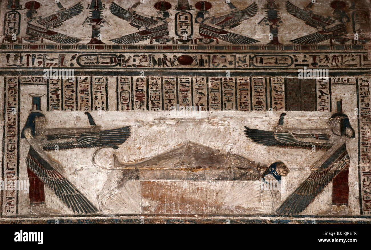 Temple decoration at Dendera, depicting the goddesses Isis and Nephthys watching over the corpse of Osiris. In religion-mythology, Death and Resurrection of Osiris is a core story of Egyptian mythology, the most famous of them all, wherein Osiris is killed by his brother Set, for insult sleeping with Set's wife Nephthys, by accident (Osiris thinking Nephthys was his wife Isis, twin sister to Nephthys), who is then chopped into pieces, then reassembled into a mummy by Isis, then resurrected by the combined powers of Isis and Thoth, who stops time long enough for the revived Osiris to magically - Stock Image