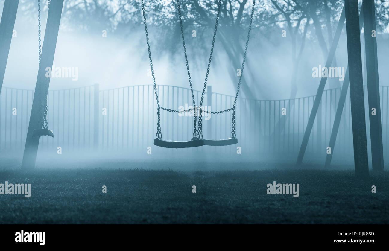 Swings in public park on a misty morning. UK - Stock Image