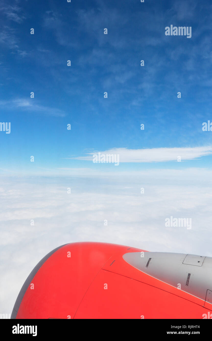 View of jet aircraft wing above the clouds - Stock Image