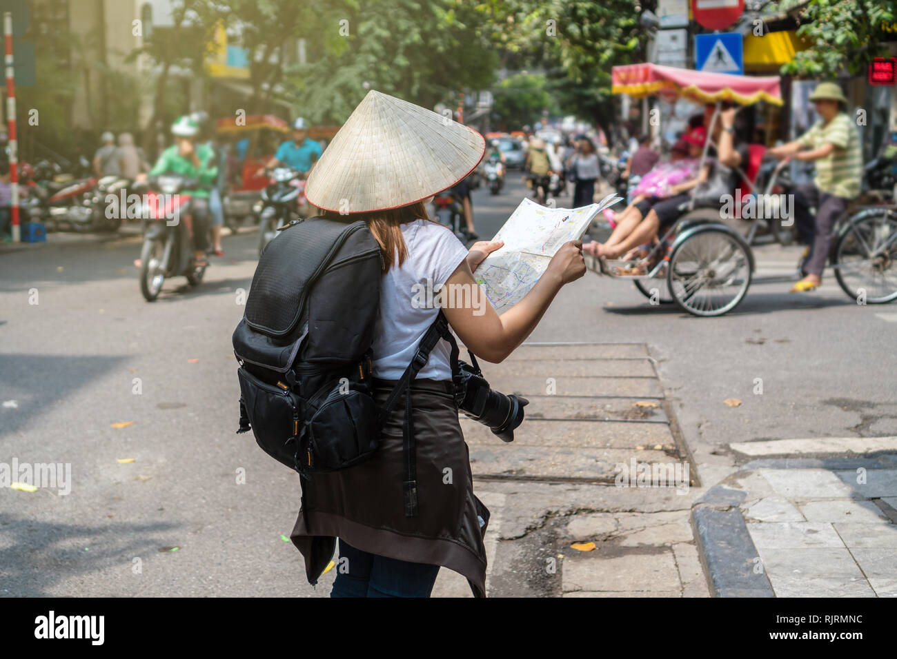Asian Traveler Holding And Looking The Map For Travel At The Hanoi