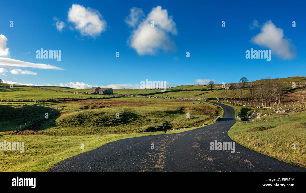 Malham Moor landscape looking stunning with blue sky, fluffy clouds and beautiful winter sun - and perfect tarmac road; a cyclist's dream! - Stock Image