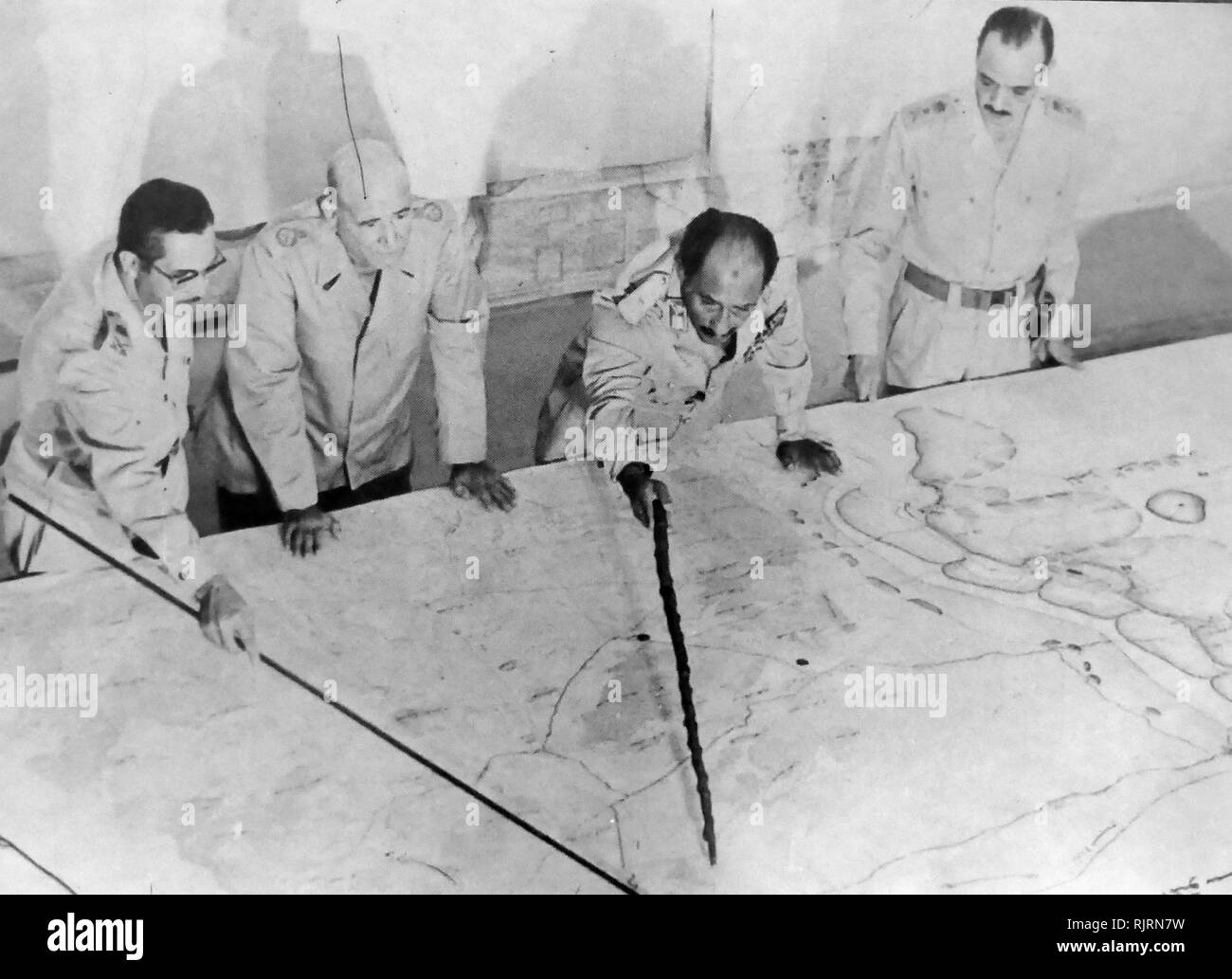 Anwar el-Sadat President of Egypt, at Military HQ during the 1973 Arab-Israeli War. He is accompanied by Field Marshall Ahmed Ismail and General Al-Gamasi. The War of 1973 (Yom Kippur War, Ramadan War, or October War), was fought from October 6 to 25, 1973, by a coalition of Arab states led by Egypt and Syria against Israel. - Stock Image