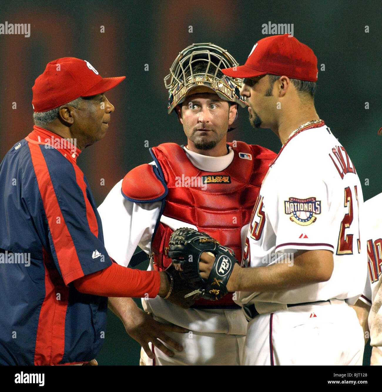 Washington, DC - July 5, 2005 -- Washington Nationals manager Frank Robinson, left, congratulates starting pitcher Esteban Loaiza (21), right, as he removes him for a relief pitcher in the ninth inning against the New York Mets at RFK Stadium in Washington, DC on July 5, 2005. Nationals catcher Brian Schneider (23) looks on from center. The Nationals withstood a ninth inning rally and beat the Mets 3 to 2.Credit: Ron Sachs/CNP.(RESTRICTION: NO New York or New Jersey Newspapers or newspapers within a 75 mile radius of New York City) | usage worldwide - Stock Image