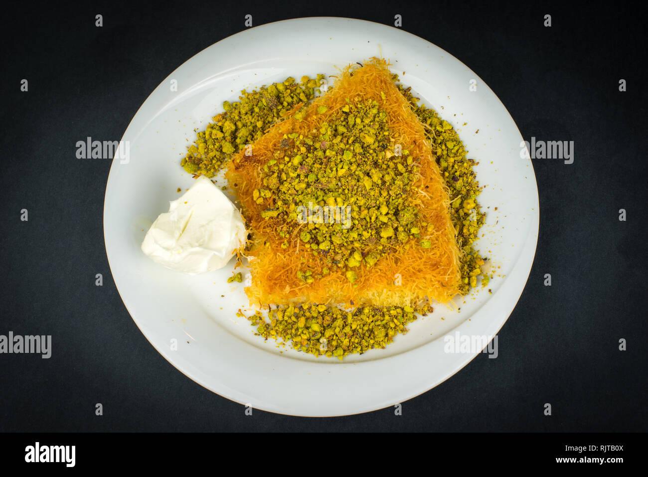 Traditional Turkish Dessert Kunefe isolated on black. Stock Photo