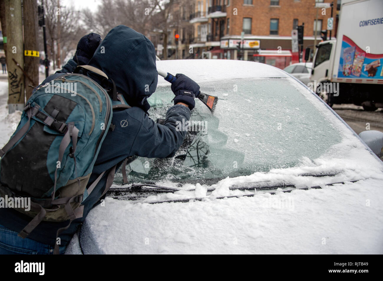 Montreal, Canada - 7 February 2019: man cleaning car windshield from ice with scraper tool. - Stock Image