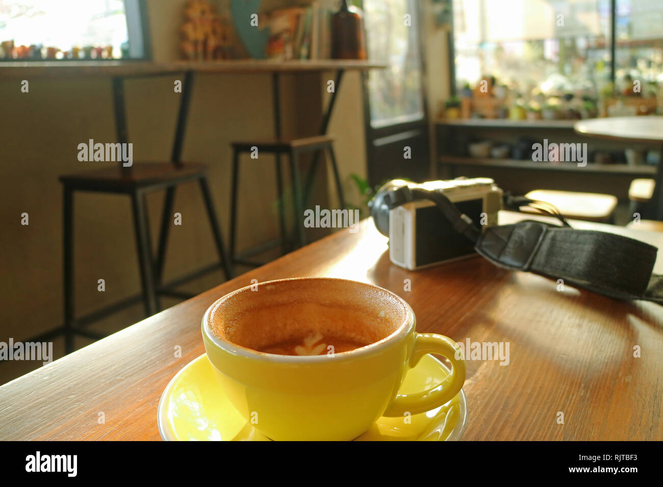 Half cup of cappuccino coffee on a wooden table with a white camera during break time - Stock Image
