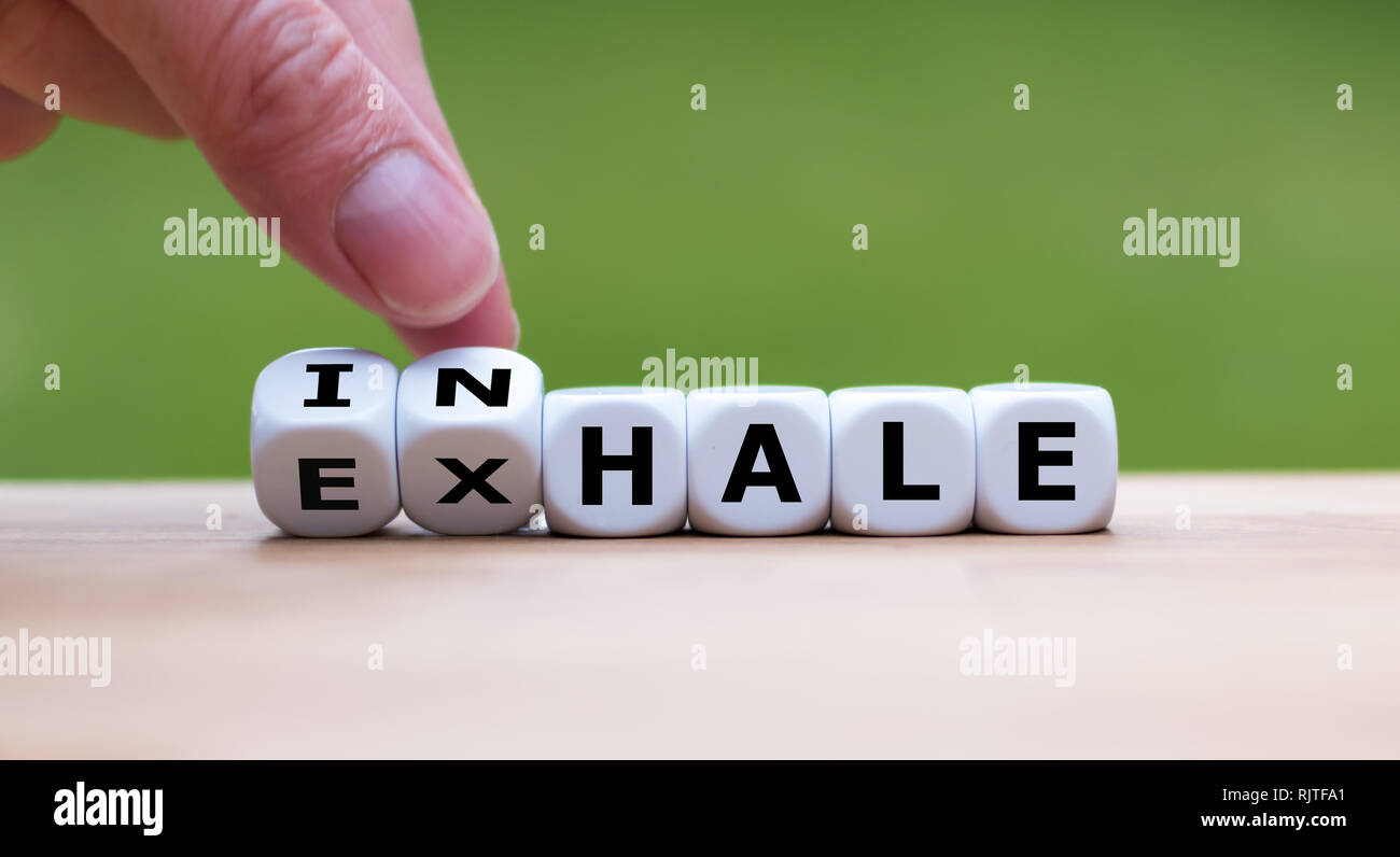Inhale,Exhale concept. Hand turns dice and changes the word 'INHALE' to 'EXHALE'. - Stock Image