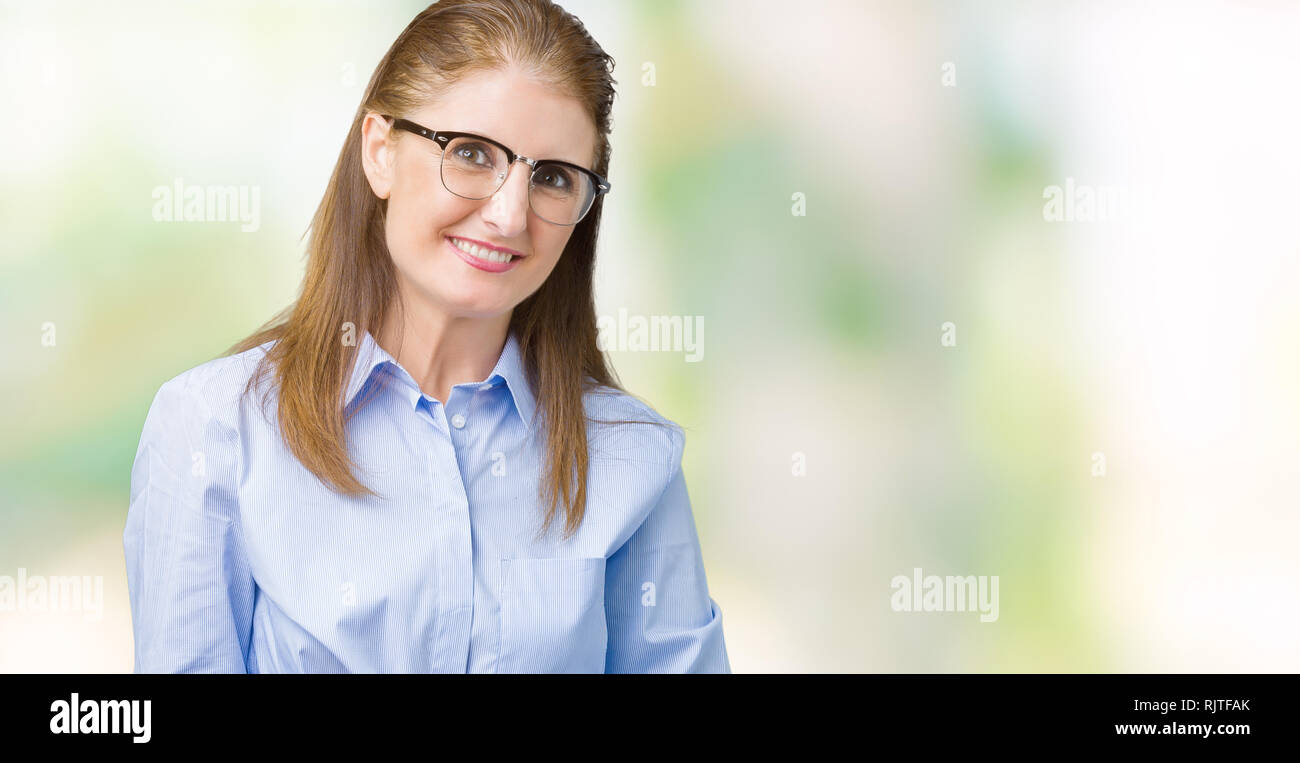 d09235f7b268 Beautiful middle age mature business woman wearing glasses over isolated  background Hands together and fingers crossed smiling relaxed and cheerful.  S