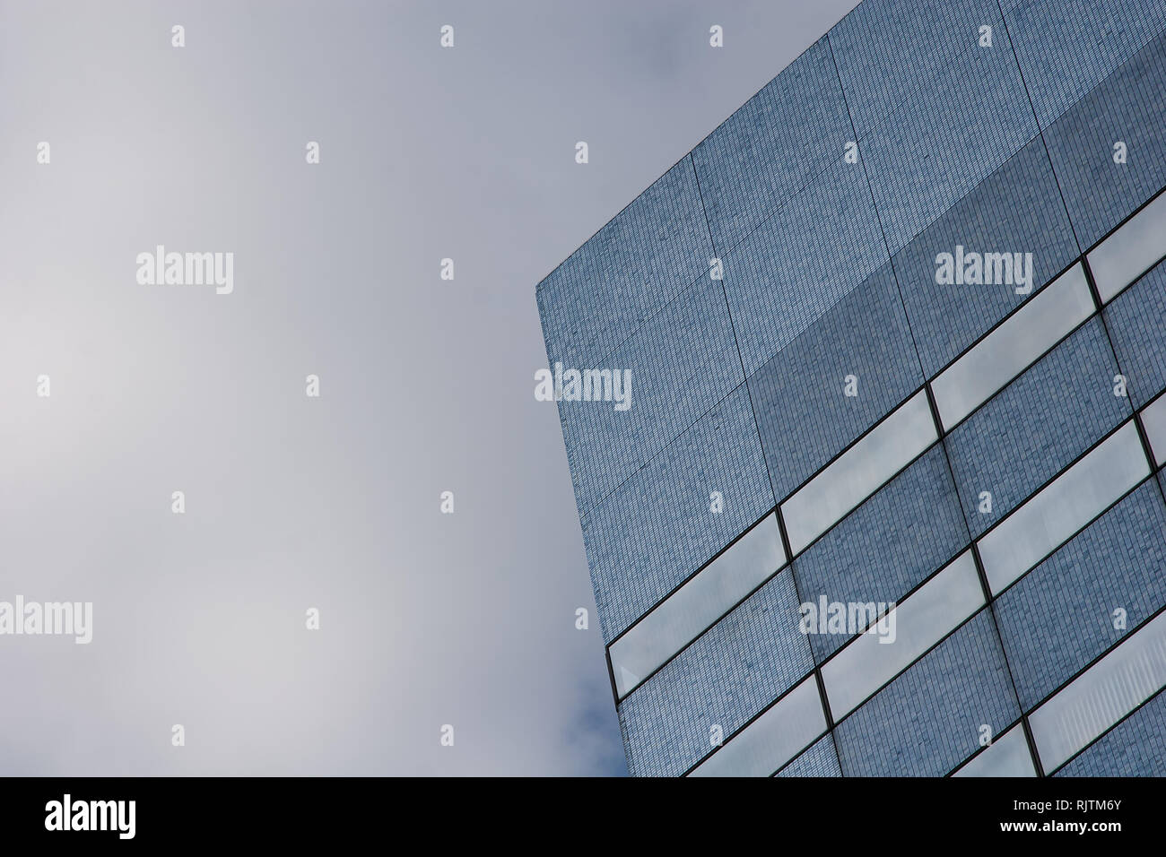 An abstract image of an office building against a cloudy sky. - Stock Image