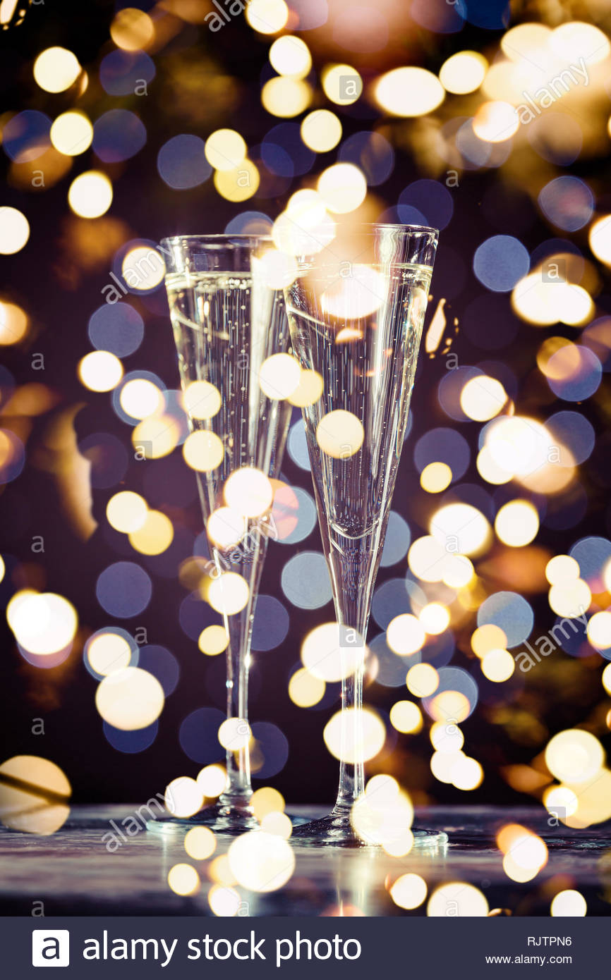 Two glasses of champagne on dark bokeh background. Holiday concept. Festive bokeh background. Vertical, toned, warm tone, bold light bokeh - Stock Image