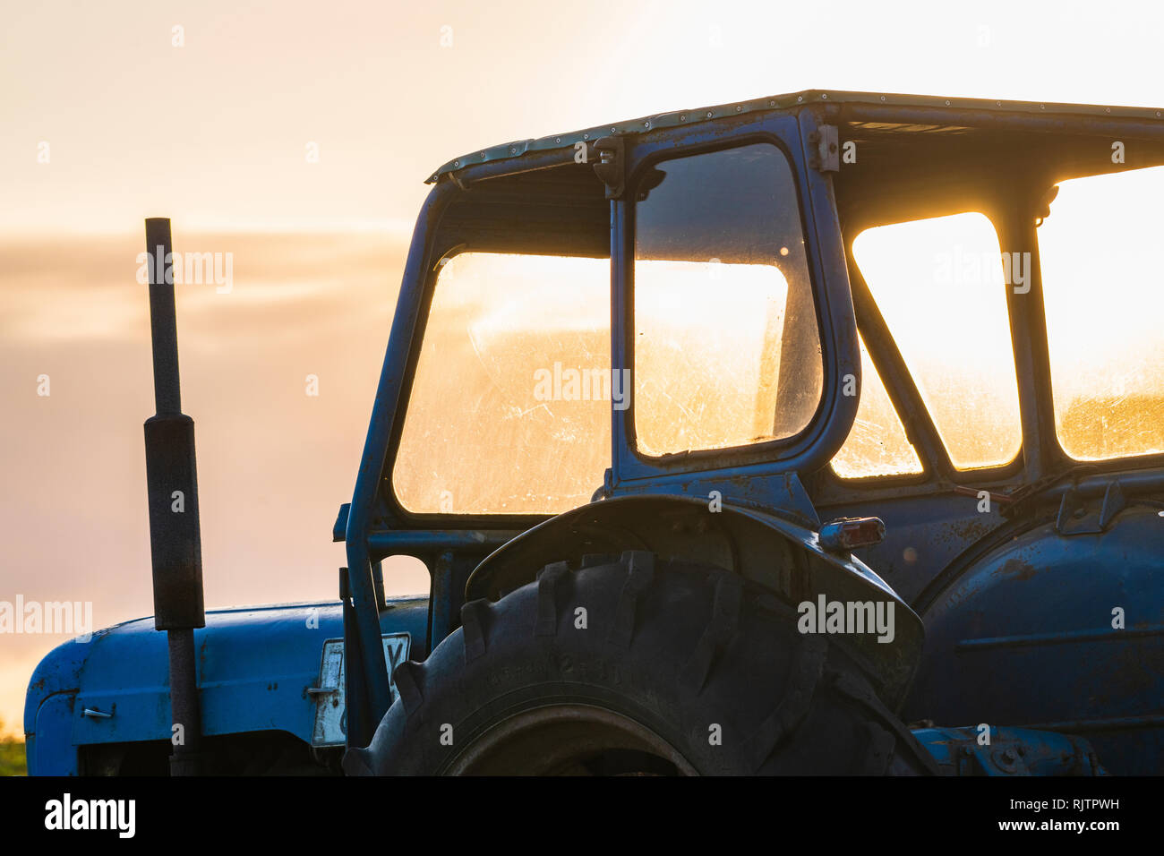 Looking through window of stationary tractor at sunrise, close up, cropped, Halland, Sweden, Europe - Stock Image