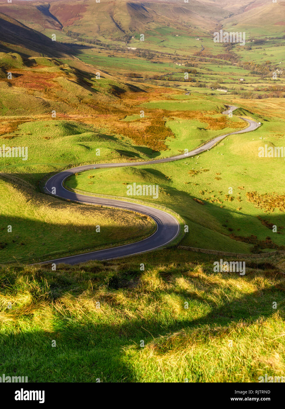 The road winds through a cleft, surrounded by towering limestone pinnacles near winnat pass, Peak district, UK. - Stock Image