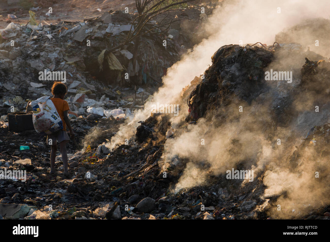 Young child collecting recyclable materials among toxic smoke from rubbish dump in Rishikesh, Uttarakhand, India - Stock Image