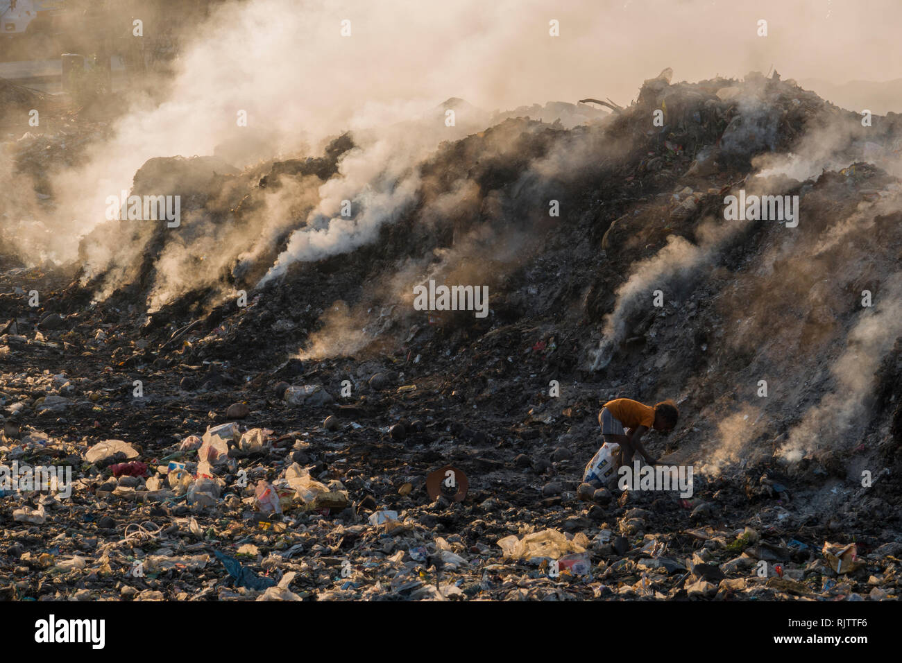 Young child collecting recyclable materials among toxic smoke from rubbish dump in Rishikesh, Uttarakhand, India Stock Photo