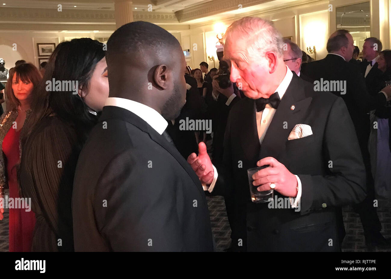 BEST QUALITY AVAILABLE The Prince of Wales speaks to young ambassadors Aisa Ali (left) and Gideon Buabeng during an Invest in Futures Reception at the Savoy in London. - Stock Image