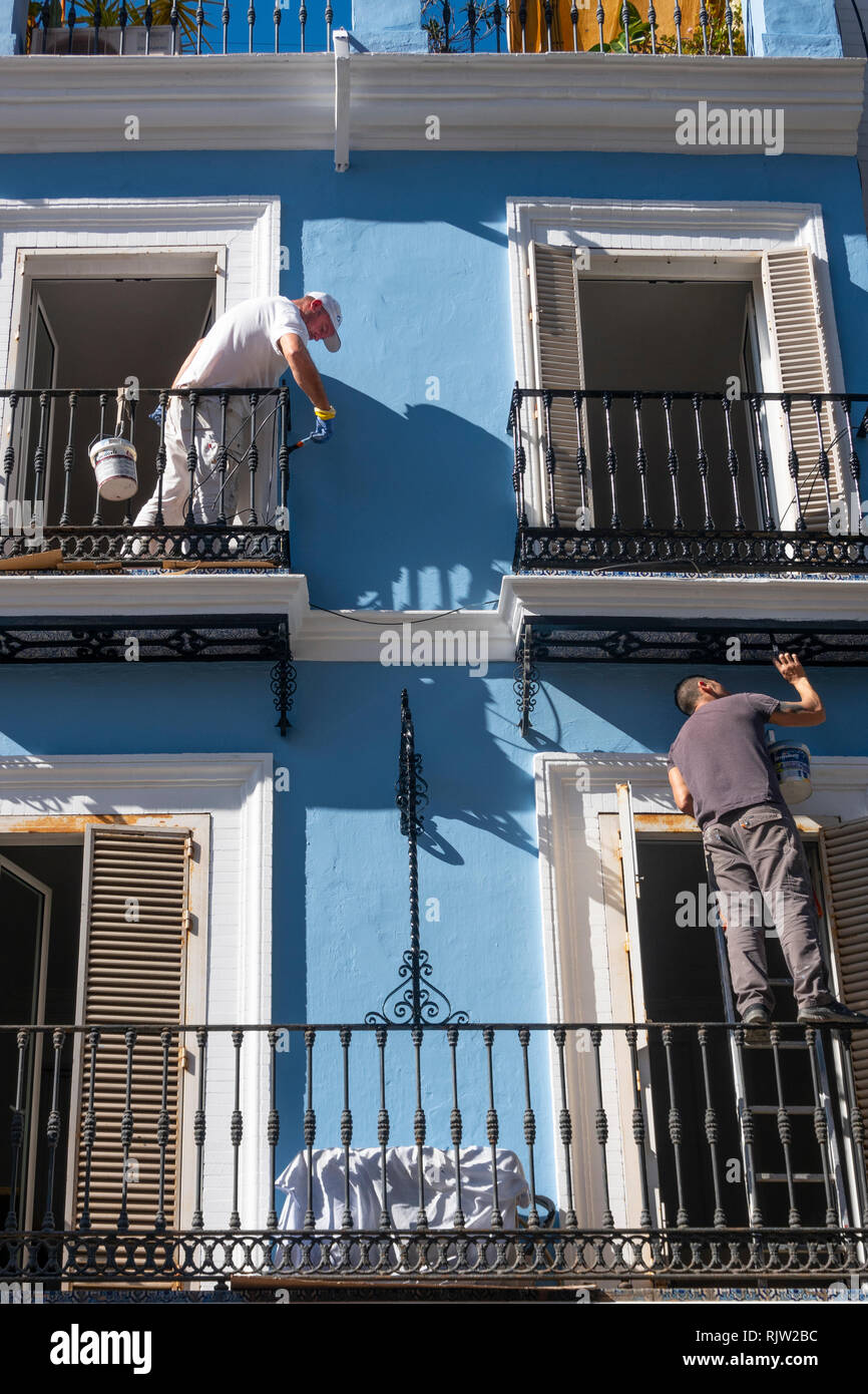 Two painter touching up the details on a house in Seville, Spain - Stock Image
