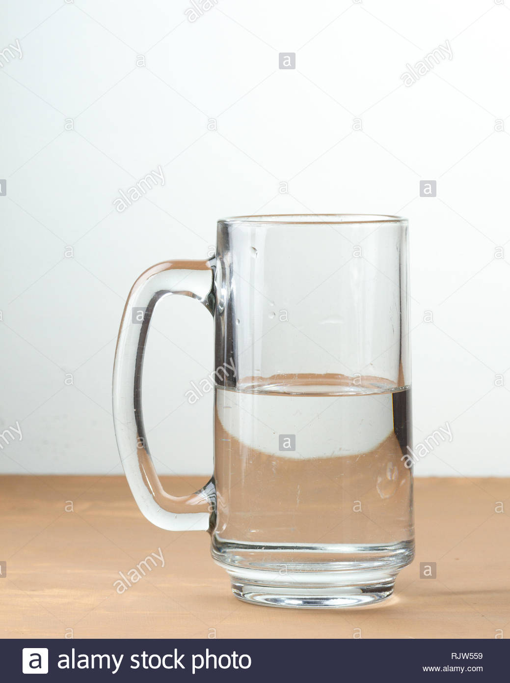 Glass half full of water on white background and wood table - Stock Image