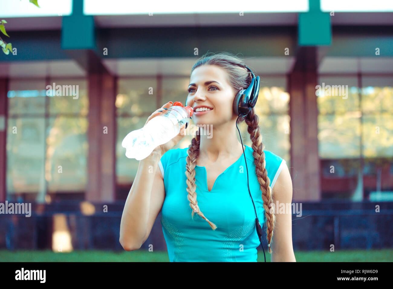 Sportive woman in headphones drinking water - Stock Image