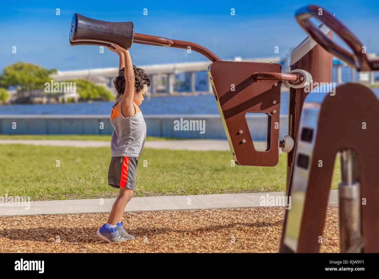 The little boy stretches high to reach the adult shoulder pads at the waterfront outdoor gym. Stock Photo