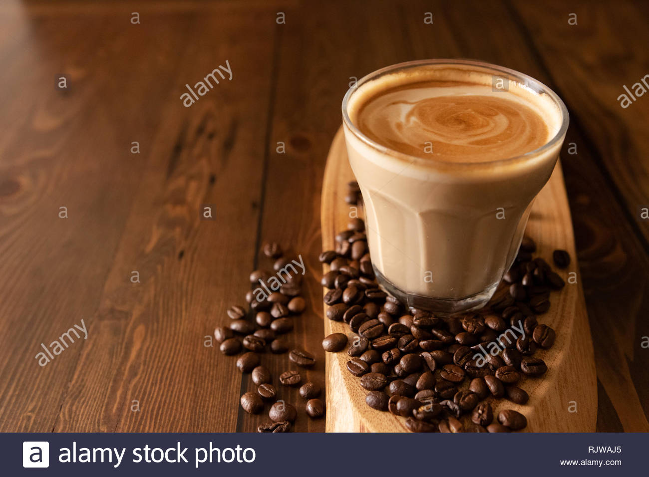 Coffee Latte Flat white in a glass with coffe beans spread out on a wooden table. Stock Photo