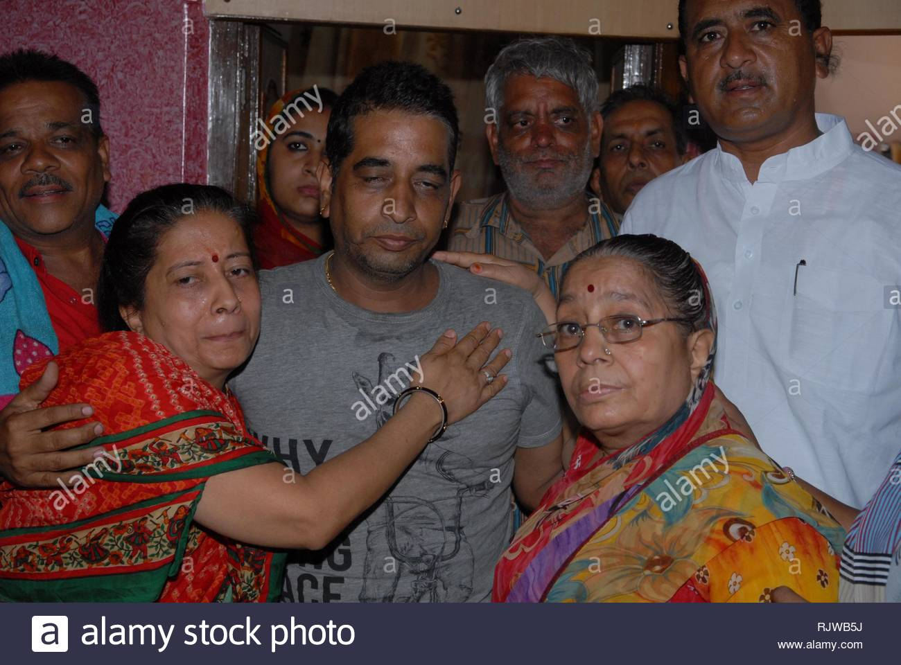 Pilgrim Mahesh Arora who was rescued and evacuated from flood-ravaged Uttarakhand, meets his relatives on arrival at Jodhpur, Rajasthan, India on June 24, 2013. Six of his relatives perished in the floods and landslides. (Sunil Verma) - Stock Image