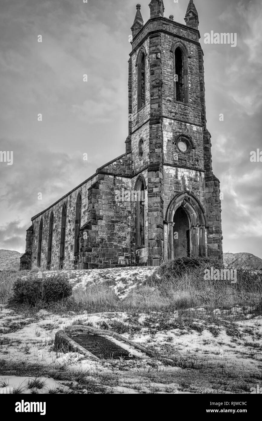 This is a moody black and white photo of the ruins of Dunlewy Church at the base of Errigal Mountain in Donegal Ireland. There is an over turned grave - Stock Image