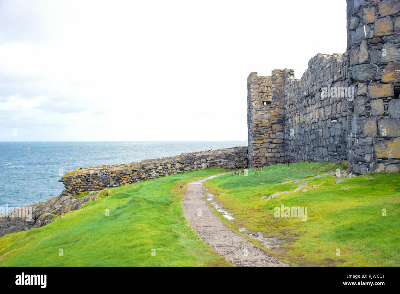 Walk path through the green grass around the great wall of Peel Castle up on St Patrick's Isle in city of Peel, Isle of Man - Stock Image