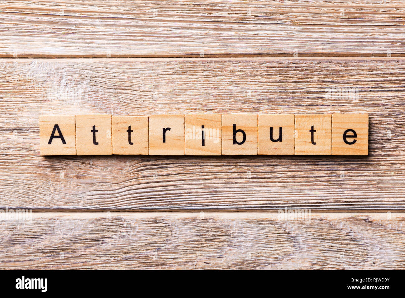 ATTRIBUTE word written on wood block. ATTRIBUTE text on wooden table for your desing, concept. - Stock Image