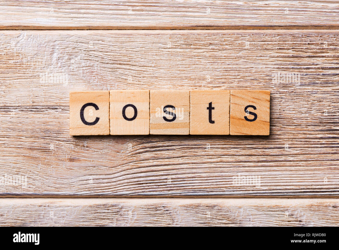 costs word written on wood block. costs text on wooden table for your desing, concept. - Stock Image