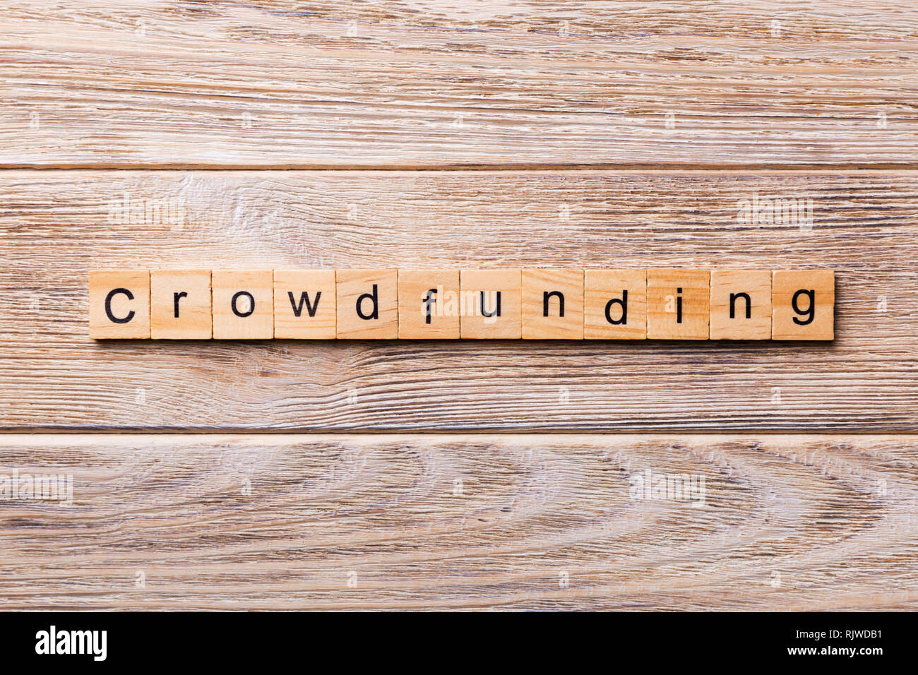 CROWDFUNDING word written on wood block. CROWDFUNDING text on wooden table for your desing, concept. - Stock Image