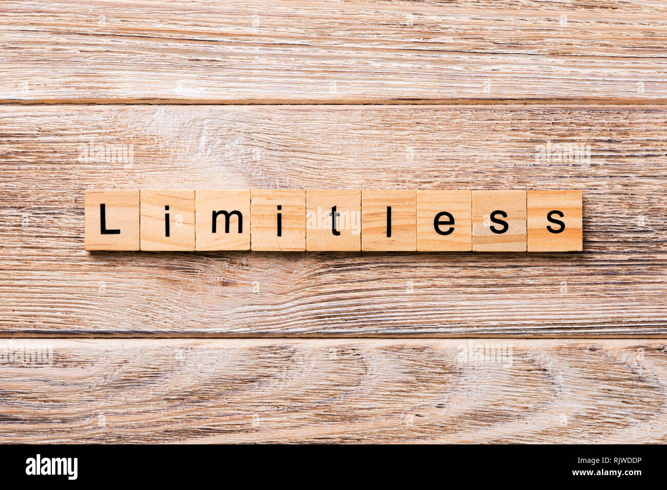 Limitless word written on wood block. Limitless text on wooden table for your desing, concept. - Stock Image