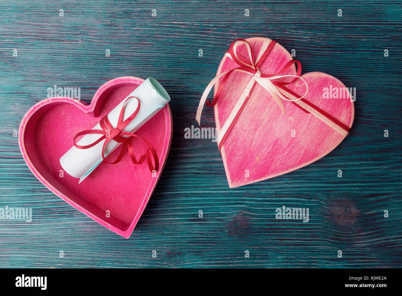 Heart shaped gift box and love letter on blue wooden background Stock Photo