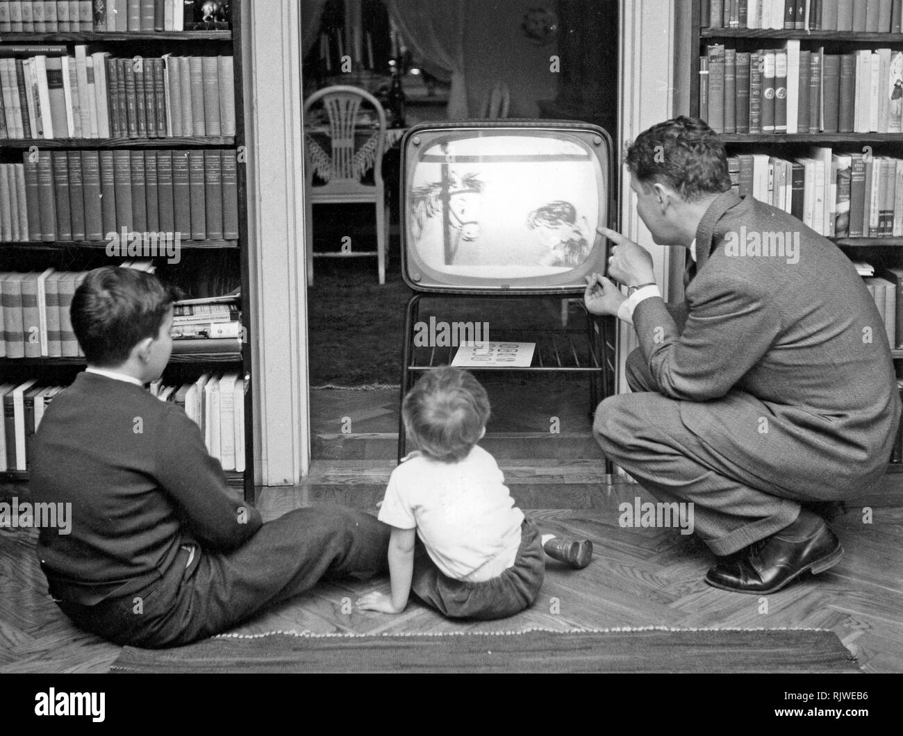 Television in the 1950s. A father with his children in front of the television set looking at a children's program. Sweden 1958 - Stock Image