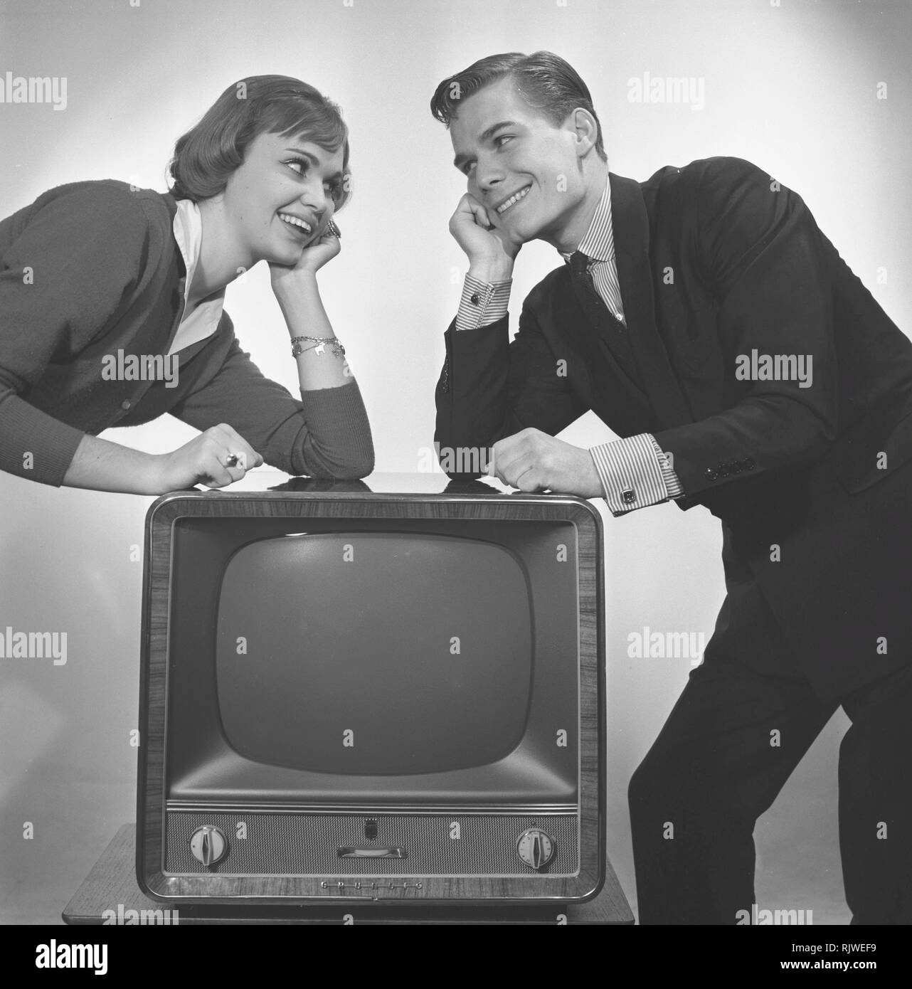 Television in the 1950s. A young couple is pictured beside a typical 50s television set.  Photo Kristoffersson ref CC93-5. Sweden 1958 Stock Photo