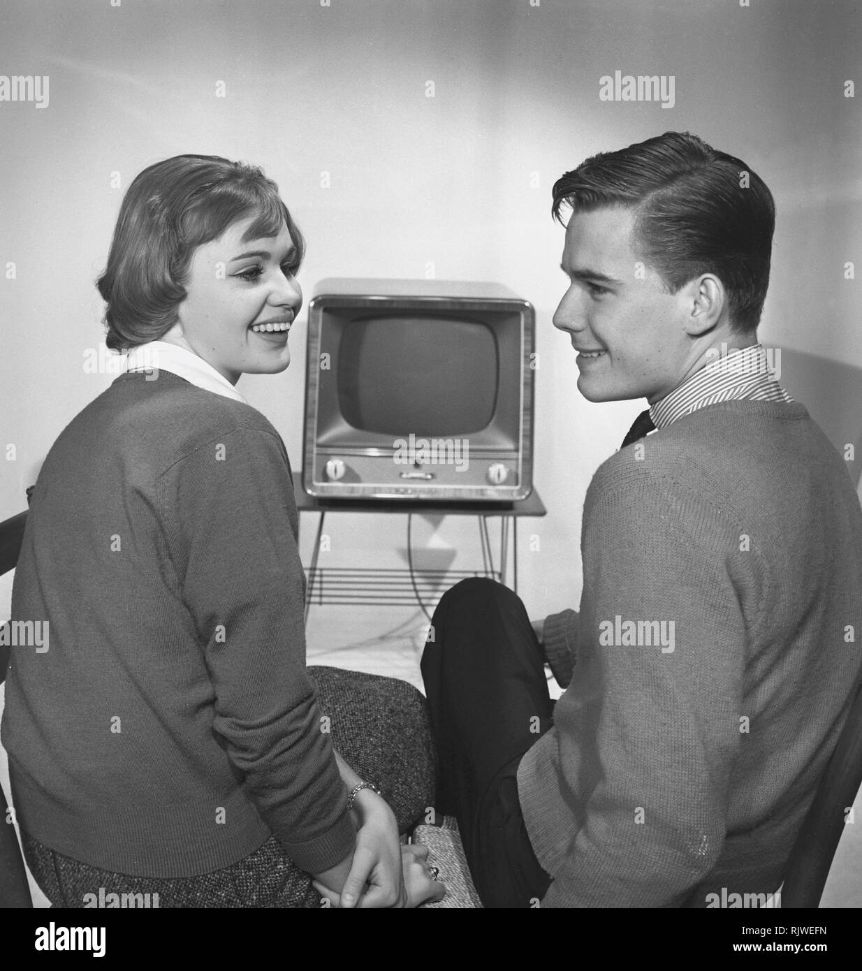 Television in the 1950s. A young couple is pictured sitting in front of a typical 50s television set.  Photo Kristoffersson ref CC93-6. Sweden 1958 - Stock Image