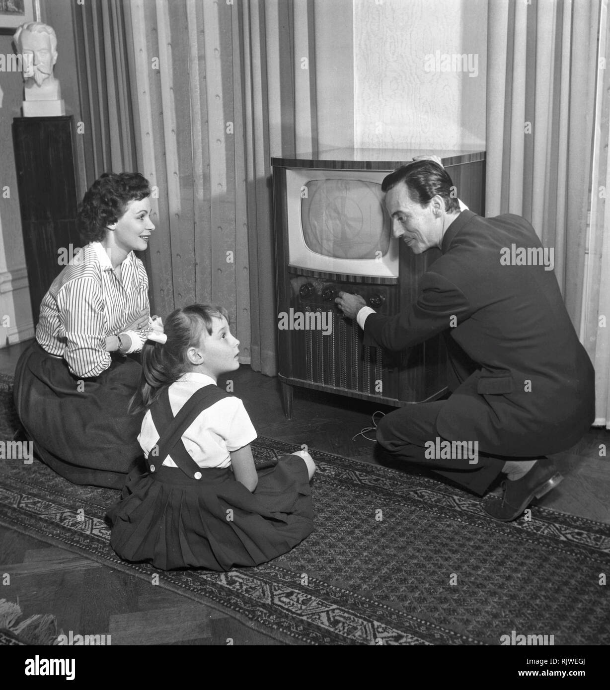 Television in the 1950s. A young couple is pictured with a typical 50s television set. The husband is adjusting the pictures and his wife and child is admiring the modern kind of home entertainment.  Photo Kristoffersson ref BU35-12. Sweden 1950s - Stock Image