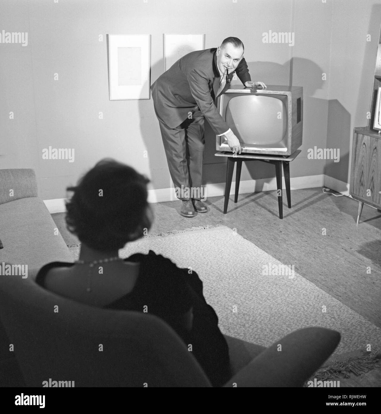 Television in the 1950s. A proud elderly man is pictured in his home with his wife with the latest in electronic home equipment visible. A typical television set on thin legs.  Photo Kristoffersson ref CD89-9. Sweden 1959 - Stock Image