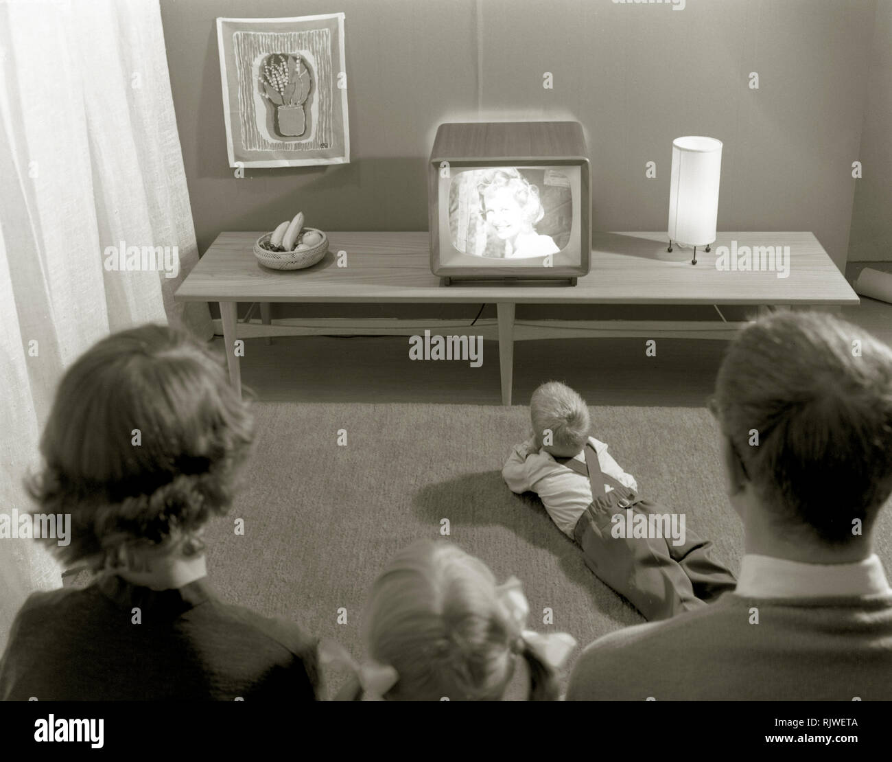 Television in the 1950s. A young couple is pictured in front of a typical 50s television set. The whole family is  admiring the modern kind of home entertainment.  Sweden 1958. ref 3789 Stock Photo