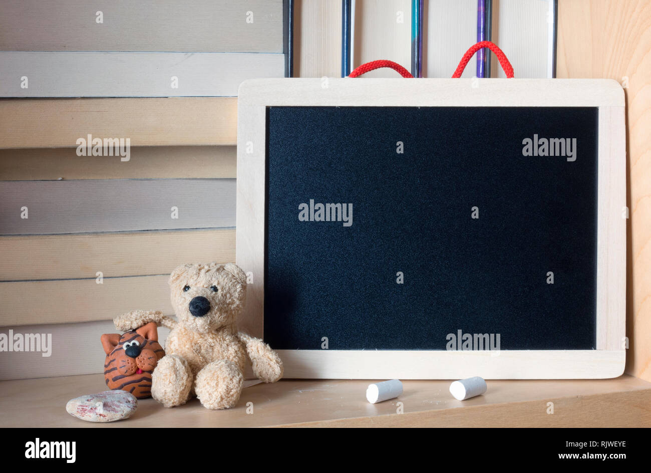 Clean wooden chalkboard on a bookshelf. Space for your text Stock Photo