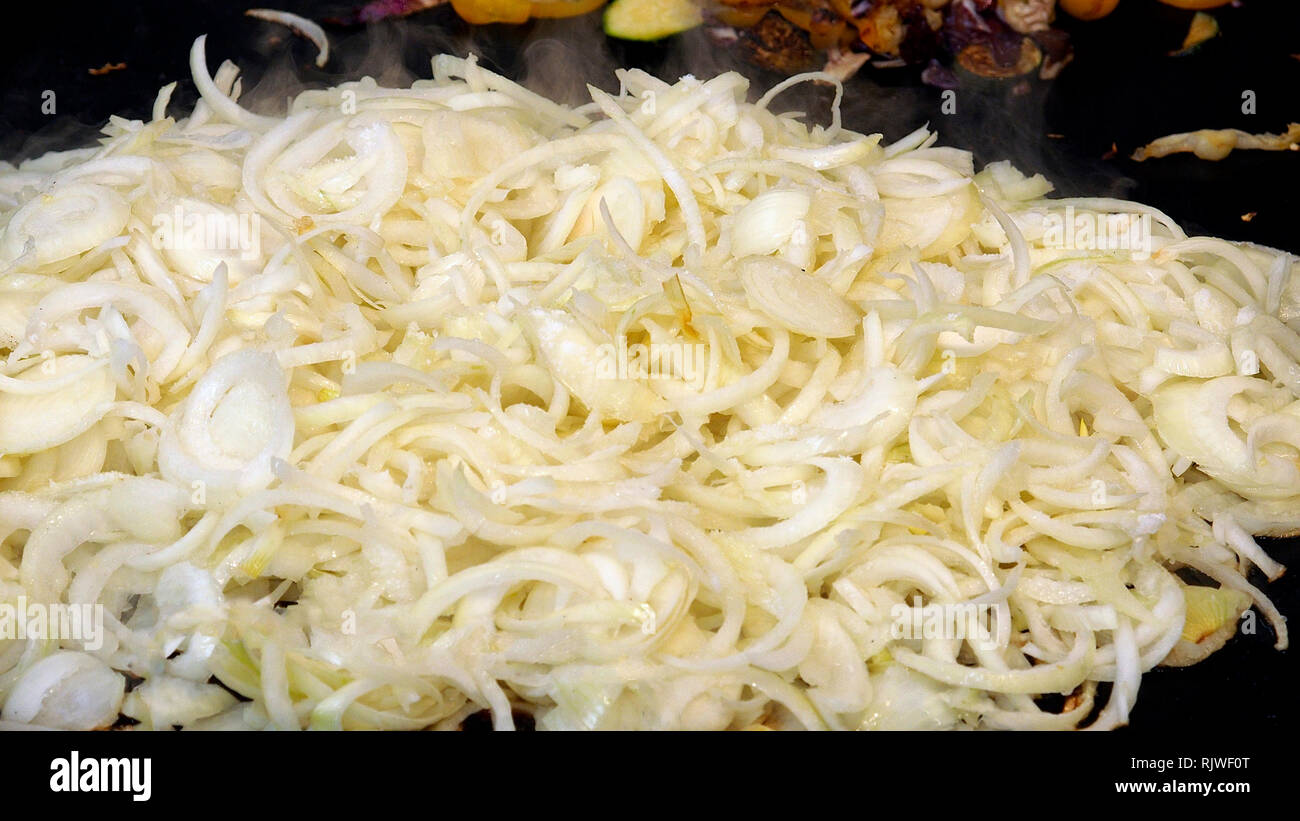 Roasting pieces of onion on big plate in the open air. Stock Photo