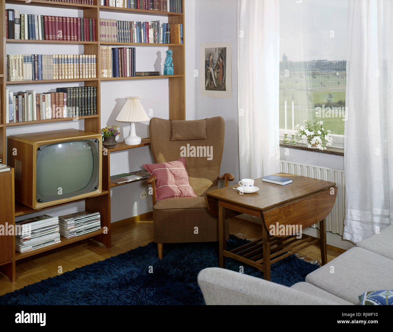 Television in the 1950s. Interior from a room with a typical 50s television set in the bookshelf.  ref BV101-5  Sweden 1958 - Stock Image