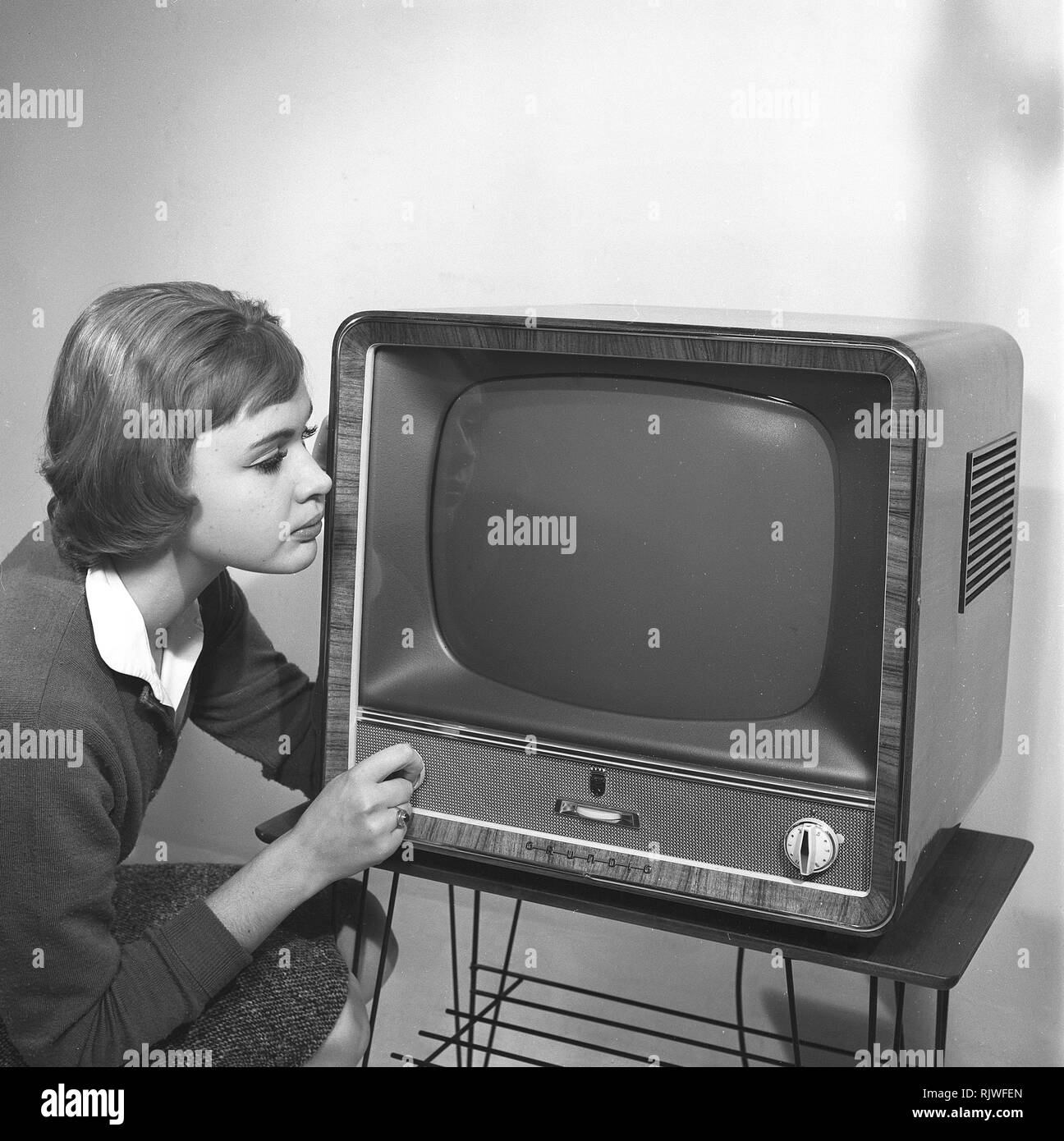 Television in the 1950s. A young woman is pictured beside a typical 50s television set. A Grundig tv standing on a typical metal string boned tv table.  Photo Kristoffersson ref CC92-12. Sweden 1958 - Stock Image