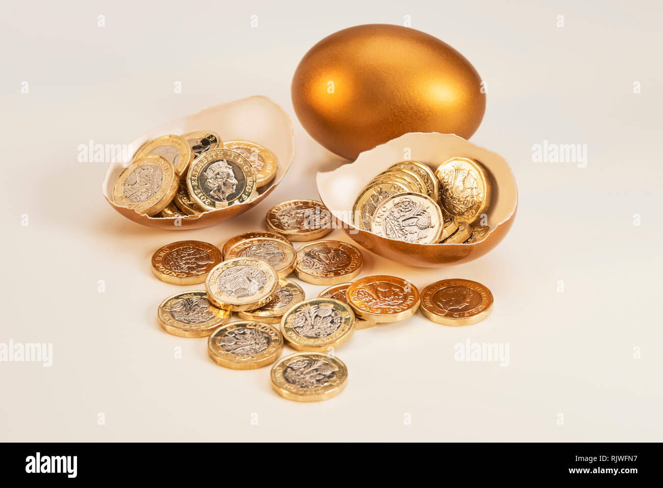 Golden Nest Egg with Shinny Pound Coins Stock Photo