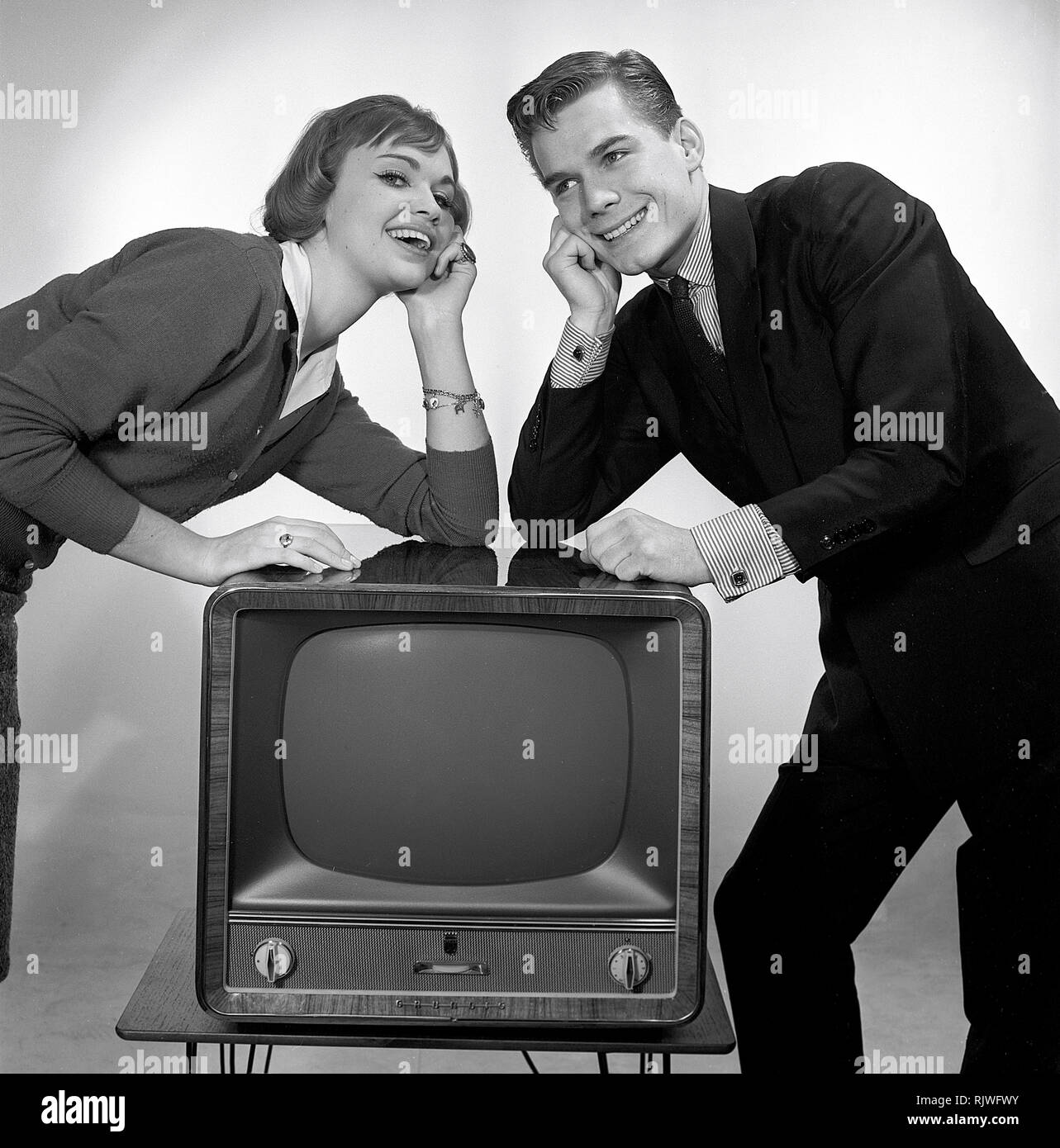 Television in the 1950s. A young couple is pictured beside a typical 50s television set.  Photo Kristoffersson ref CC93-3. Sweden 1958 Stock Photo