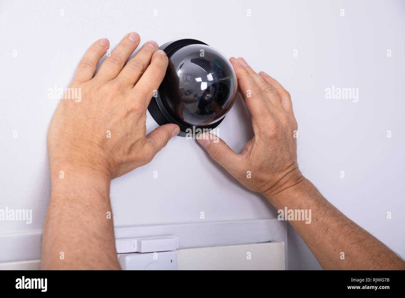 Close-up Of Male Technician Hand Installing Surveillance Camera On Wall - Stock Image