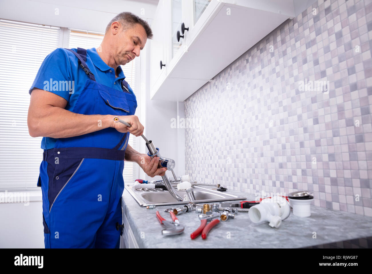 Side View Of A Plumber Fixing Water Tap In Kitchen Stock Photo