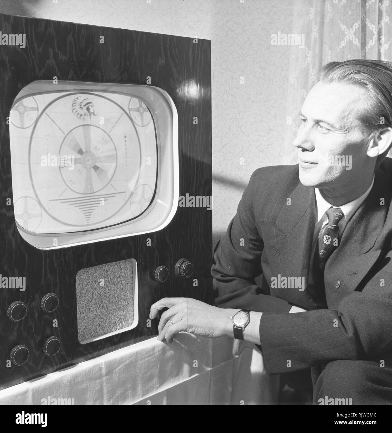 Television in the 1950s. A man with an early television set adjusting the picture. November 1953 - Stock Image