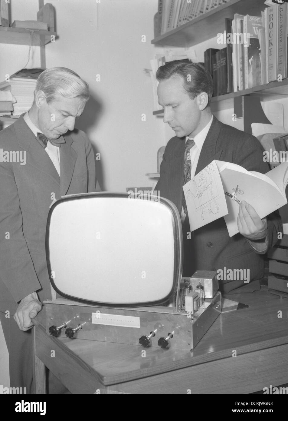 Television in the 1950s. A man with an early television set in production or testing at the Elfo company is experimenting with television technology. January 1954 - Stock Image